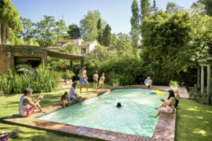Multi-generation family with parents and children relaxing and swimming in their backyard pool outside of their home.