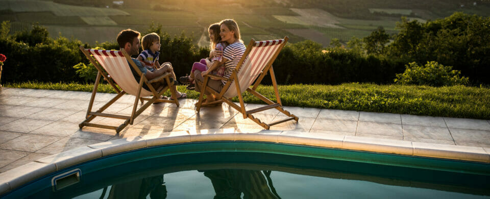 A happy family having fun and sitting on deck chairs by their home backyard pool with the sunset in the background.