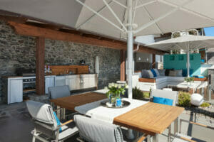 Pool area with a complete equipment for an outdoor kitchen and dining area.