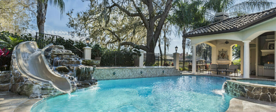 Home swimming pool trends showing a spa and swimming pool with slide and waterfall.