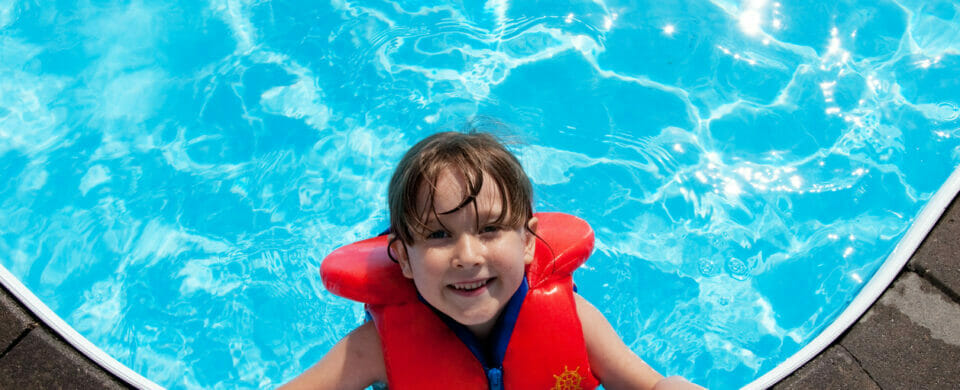 Little girl wearing pool safety equipment while enjoying a day in the pool.