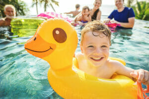 Family spending their day at the pool with the children using different pool floats and toys.