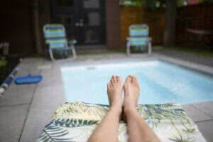 Person relaxing in a small pool at home, showing backyard in the background.