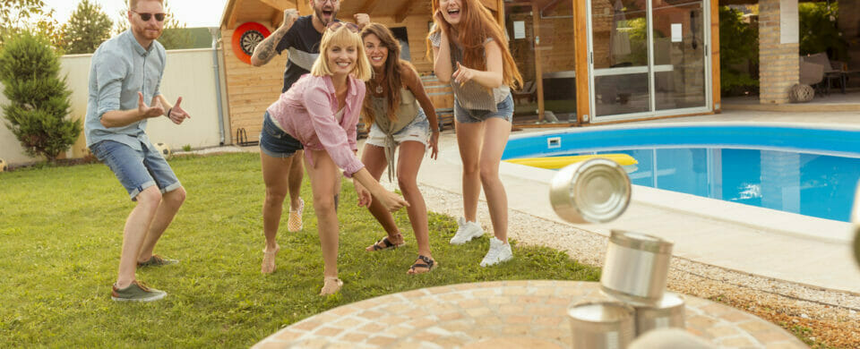 Group of friends playing knock down tin can games during a holiday backyard pool party.