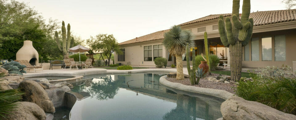 Desert landscaping ideas for a home backyard pool, featuring desert plants and other rock elements.