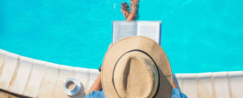 Photo of a man having a great poolside reading activity, spending a day at the pool reading a good book.