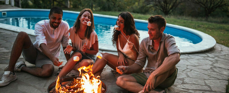 Group of friends by their pool area gathered around a fire while eating toasted marshmallows; concept of fun fall ideas.