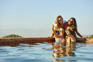Group of women unwinding by the pool, taking pictures during a mom pool party.